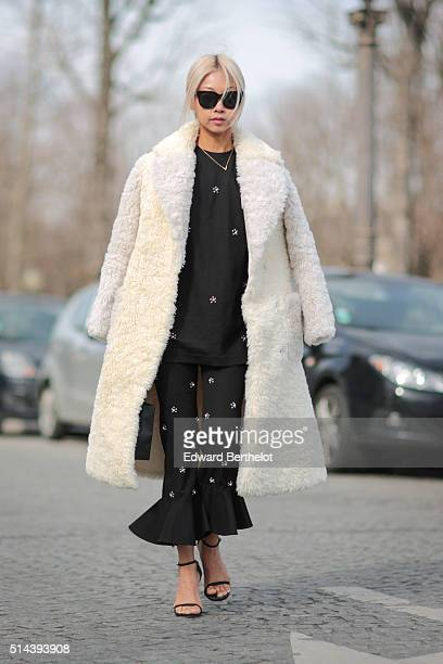 A guest is wearing a white coat and a black dress after the Chanel show during Paris Fashion Week Womenswear Fall Winter 2016/2017 on March 8 2016 in...