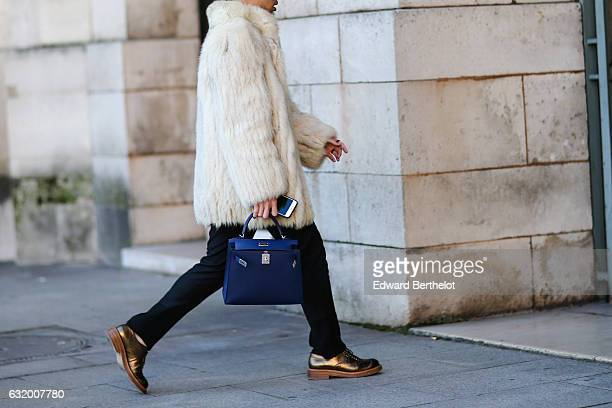 A guest is wearing a white fur coat a Hermes blue bag black pants and brown shiny shoes after the Balenciaga show during Paris Fashion Week Menswear...