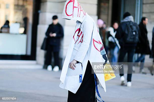 A guest is wearing a white hoodie coat with cartoon prints a pink bag black pants yellow socks and white shoes with red lace after the Balenciaga...