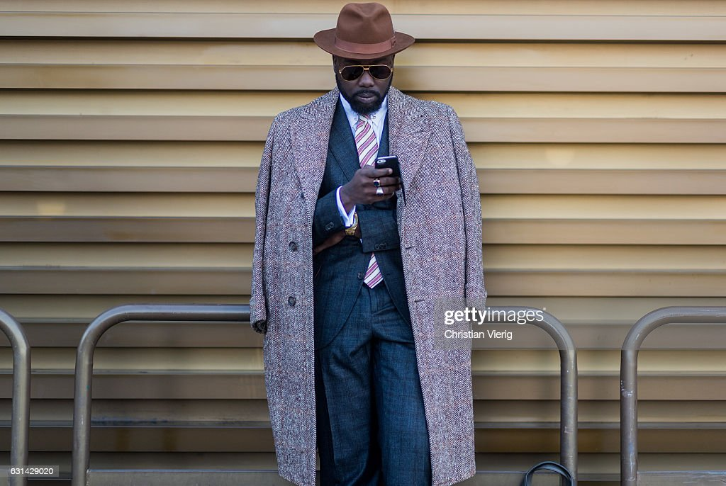 A guest is wearing a wool coat, suit, hat and sunglasses on January 10, 2017 in Florence, Italy.