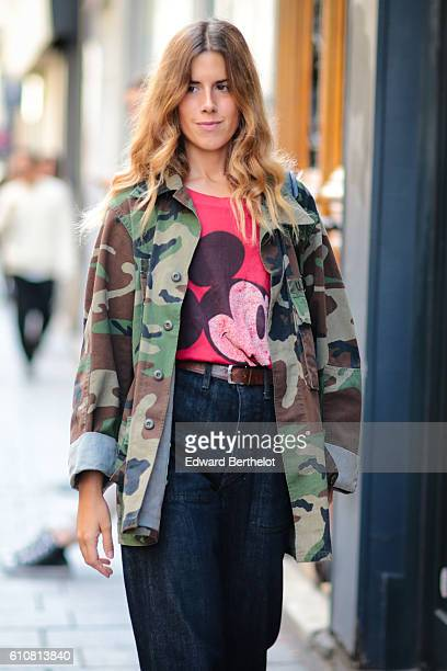 A guest is wearing green camo jacket a red Mickey Mouse tshirt a brown belt and blue denim jeans outside the Aalto show at Paris Fashion Week Spring...