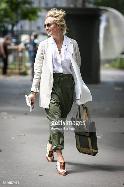 A guest is wearing green pants a green bag a white shirt and a white jacket before the Issey Miyake Men show during Paris Fashion Week Menswear...