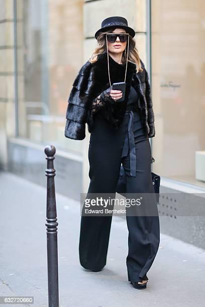 A guest is wearing sunglasses a black hat a black faux fur coat gloves and black pants outside the Elie Saab show during Paris Fashion Week Haute...