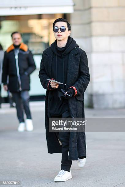 A guest is wearing sunglasses a black hoodie a black long coat black pants and white sneakers shoes after the Balenciaga show during Paris Fashion...