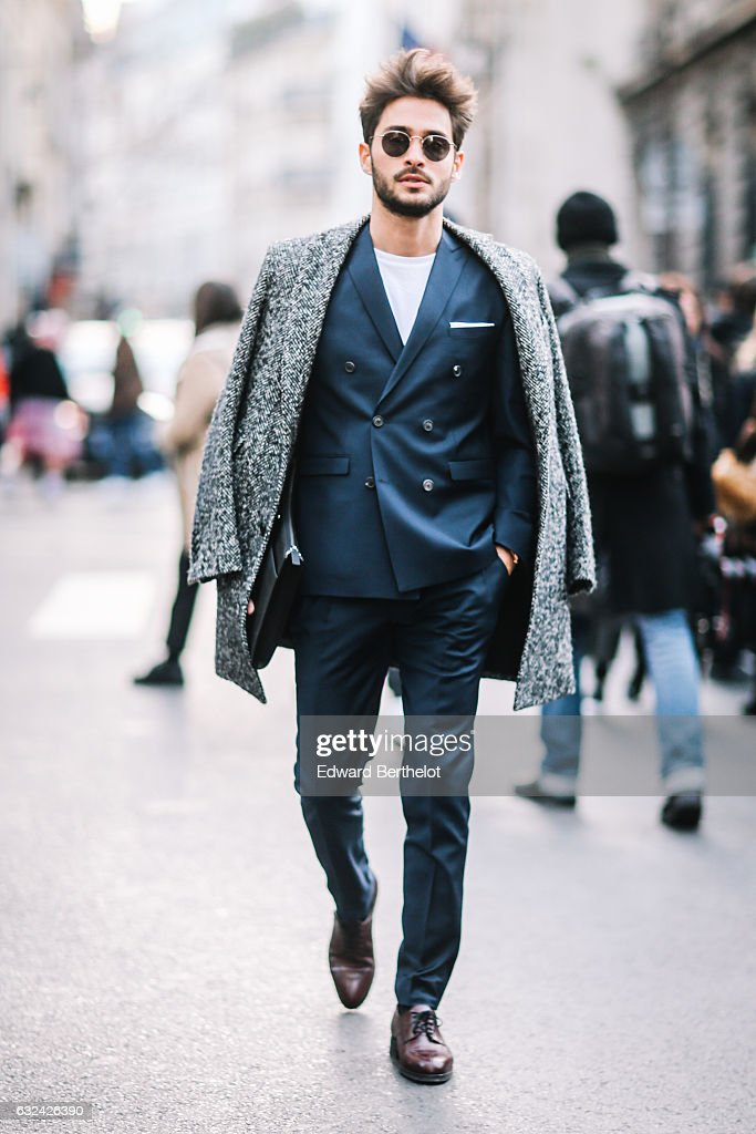 A guest is wearing sunglasses, a coat, a blue suit and brown leather shoes, outside the Paul Smith show, during Paris Fashion Week Menswear Fall/Winter 2017/2018, on January 22, 2017 in Paris, France.