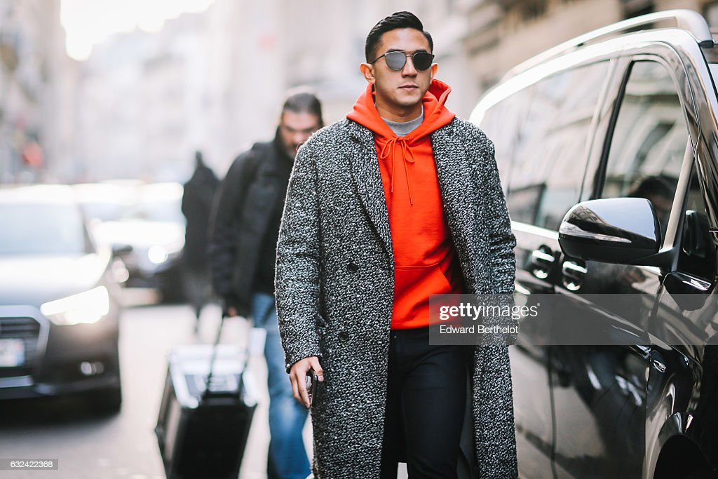 A guest is wearing sunglasses, and orange hoodie, a wool coat, and black pants, outside the Paul Smith show, during Paris Fashion Week Menswear Fall/Winter 2017/2018, on January 22, 2017 in Paris, France.