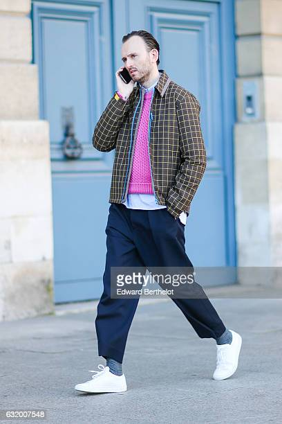 A guest is wearing white shoes blue pants a brown jacket and a pink top after the Balenciaga show during Paris Fashion Week Menswear Fall/Winter...