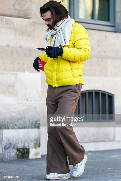A guest is wearing white shoes brown pants a yellow winter coat blue gloves and a white scarf after the Balenciaga show during Paris Fashion Week...