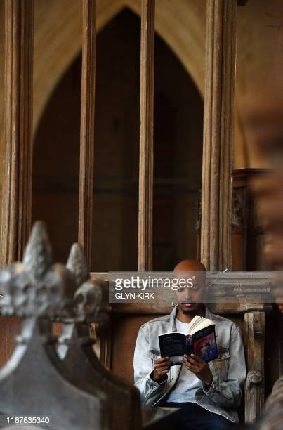 Guest Ismail Abdirahman reads during his stay at St Mary's Church where guests can pay to stay overnight in what is known as 'champing' in...