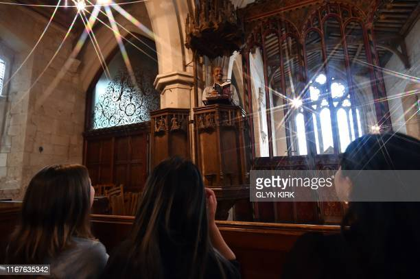Guest Ismail Abdirahman reads to his friends Andrea Stewart Lingbo Zhou and Kae Ono from the pulpit at St Mary's Church where guests can pay to stay...