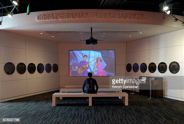 A guest looks at a footage of Prince and Beyonce's performance at the 46th Grammy Awards in the Great Grammy Performances theater in memory of...