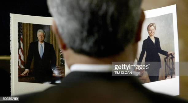 A guest looks at the program showing the official White House portraits for former US president Bill Clinton and US Senator Hillary Clinton during...