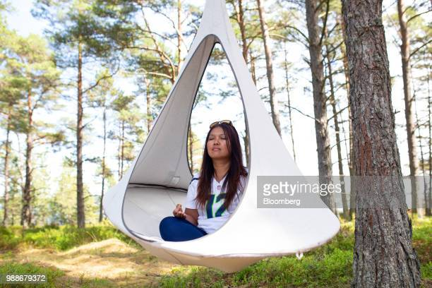 A guest mediates in a suspended pod chair on SuperShe island near Raasepori Finland on Wednesday June 27 2018 The price of experimental networking on...