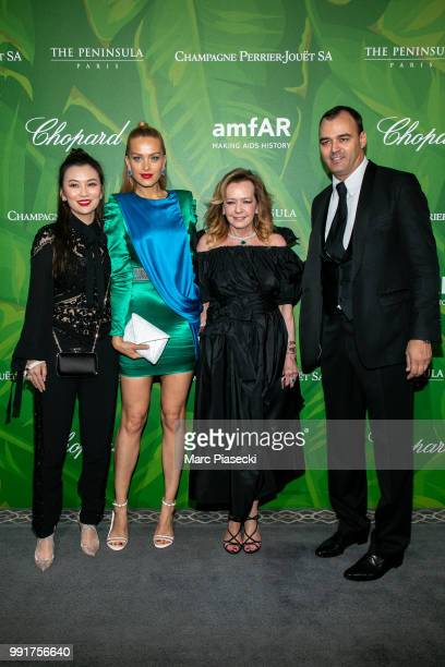 A guest model Petra Nemcova Caroline Scheufele and Milutin Gatsby attend the amfAR Paris Dinner 2018 at The Peninsula Hotel on July 4 2018 in Paris...