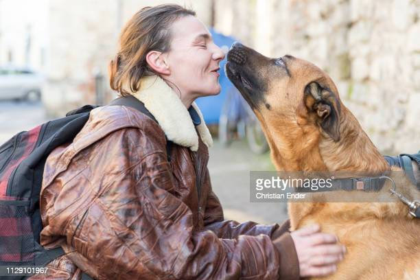 """Guest of the utility plays with a dog in front of the entrance. Volunteers help with lunch in Göttingen in the so called """"Mittagstisch"""", an offer..."""