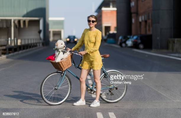 A guest on a bike with her dog wearing a yellow dress outside Stine Goya on August 09 2017 in Copenhagen Denmark