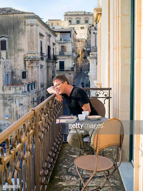 A guest on a private guestroom terrace at Seven Rooms Villadorata in Noto Sicily a former residence of Prince Giacomo Nicolaci now a small luxury...