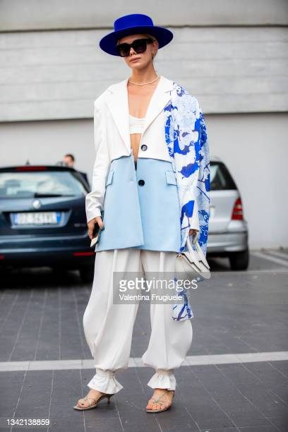 Guest outside Etro fashion show wearing a blue hat, sunglasses, white, printed and turquoise patched jacket during the Milan Fashion Week - Spring /...