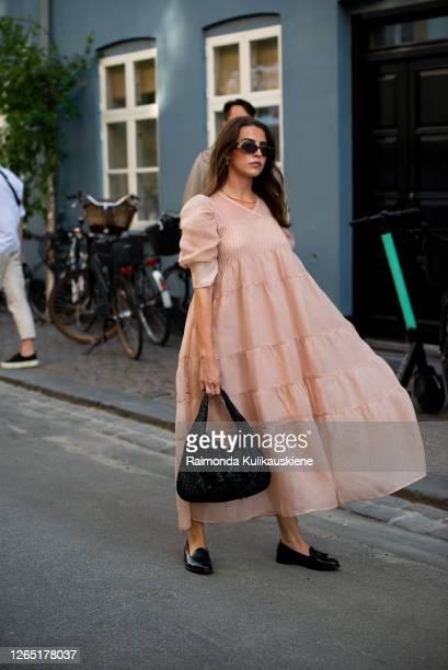 Guest outside Ganni wearing nude color dress and black bag during Copenhagen fashion week SS21 on August 10, 2020 in Copenhagen, Denmark.