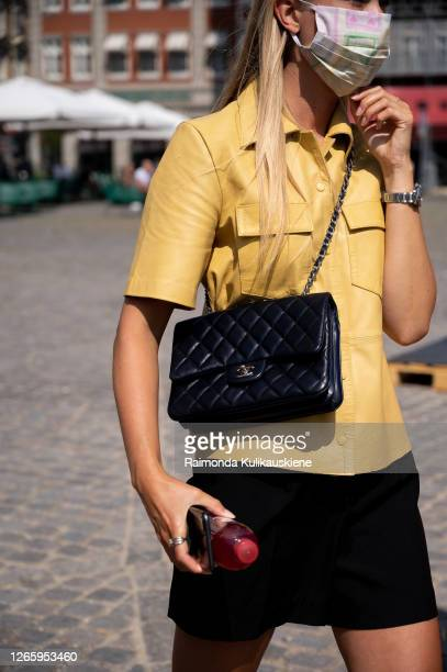 Guest outside Helmstedt wearing black shorts yellos leather shirt and black Chanel bag during Copenhagen fashion week SS21 on August 12 2020 in...