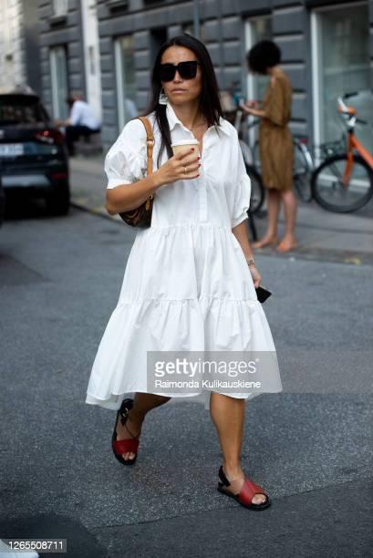 Guest outside Malaikaraiss wearing white dress and holding coffee during Copenhagen fashion week SS21 on August 10, 2020 in Copenhagen, Denmark.