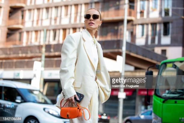 Guest outside Max Mara fashion show wearing white pants suit, orange bag and zebra boots during the Milan Fashion Week - Spring / Summer 2022 on...