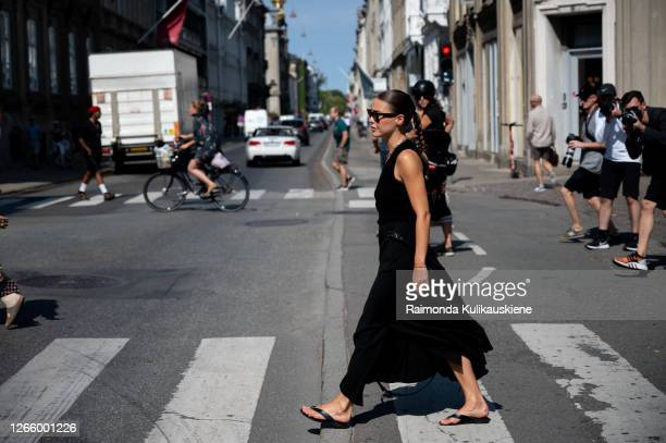 Guest outside MFPEN wearing black dress crossing the road during Copenhagen fashion week SS21 on August 12 2020 in Copenhagen Denmark