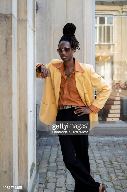 Guest outside MFPEN wearing black pants brown shirt and yellow jacket during Copenhagen fashion week SS21 on August 12 2020 in Copenhagen Denmark