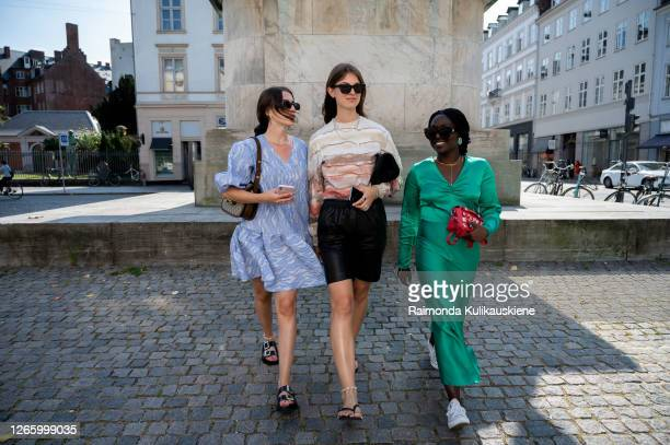 Guest outside MFPEN wearing blue dress black leather shorts with beige top and green silk dress during Copenhagen fashion week SS21 on August 12 2020...