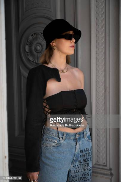 Guest outside MFPEN wearing jeans with words black lives matter black corset top black short denim jacket and black bucket hat during Copenhagen...