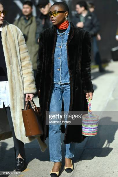 Guest pairs denim pieces, ballet flats, and a faux fur winter coat outside of Spring Studios during New York Fashion Week Fall/Winter '20 on February...