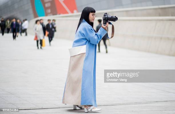 A guest photographing with her Canon DSLR camera wearing blue coat is seen at the Hera Seoul Fashion Week 2018 F/W at Dongdaemun Design Plaza on...