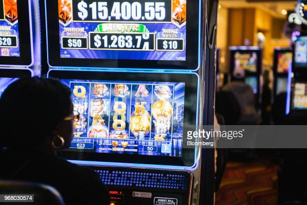 A guest plays a slot machine on the gaming floor during the launch of fullscale sports betting at Dover Downs Hotel and Casino in Dover Delaware US...