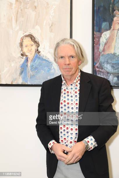 Guest poses by a portrait from the Unmissable25 exhibition during the private view of The Other Art Fair at The Old Truman Brewery on March 14, 2019...