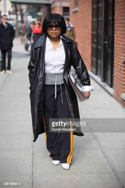 A guest poses outside of the Lanyu show wearing a black coat during New York Fashion Week on February 10 2019 in New York City