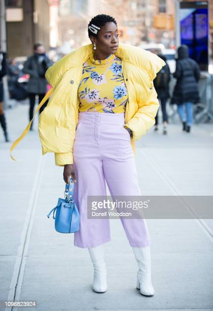 Guest poses outside of the Son Jung Wang show during New York Fashion Week wearing a yellow coat, yellow floral print shirt, light purple pants,...