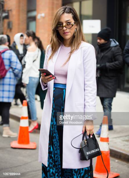 A guest poses outside of the Tibi show wearing a light pink jacket blue pants and holding a black Balenciaga purse during New York Fashion Week on...