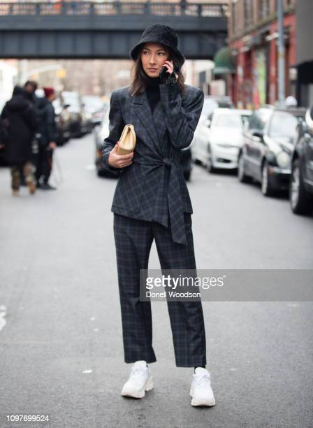 Guest poses outside of the Tibi show wearing a plaid suit with white sneakers during New York Fashion Week on February 10, 2019 in New York City.