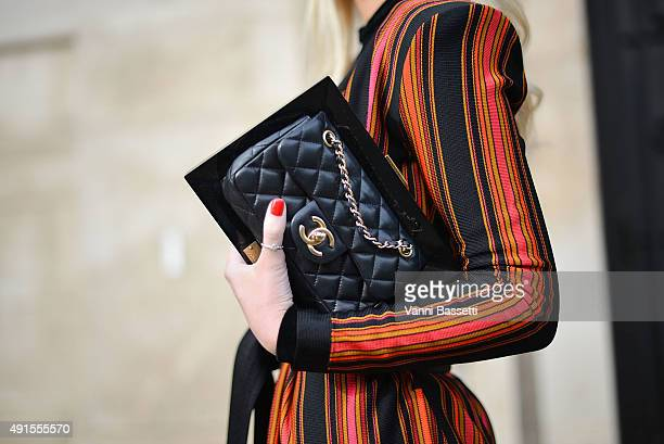 A guest poses wearing a Balmain dress and a chanel clutch before the Chanel show at the Grand Palais during Paris Fashion Week SS16 on October 6 2015...