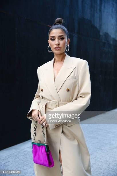 A guest poses wearing a beige coat and pink handbag outside the Jason Wu show during New York Fashion Week on September 08 2019 in New York City