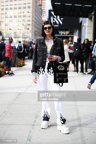Guest poses wearing a black jacket and white pants and black handbag outside of Spring Studios during New York Fashion Week on September 08, 2019 in...
