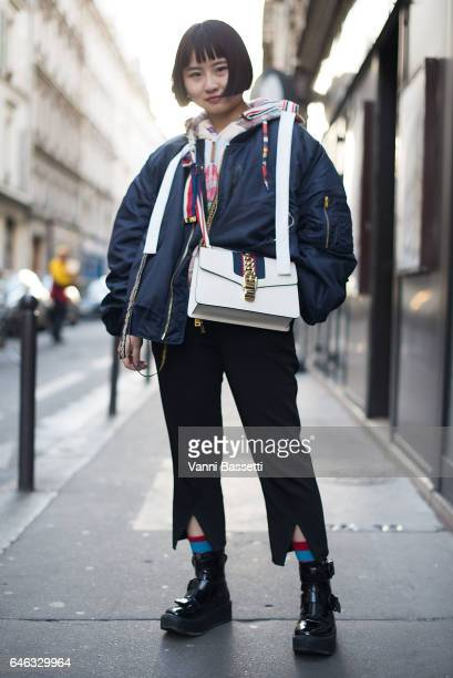 A guest poses wearing a bomber jacket and a Gucci bag before the Koche show at the Folies Bergere during Paris Fashion Week Womenswear FW 17/18 on...