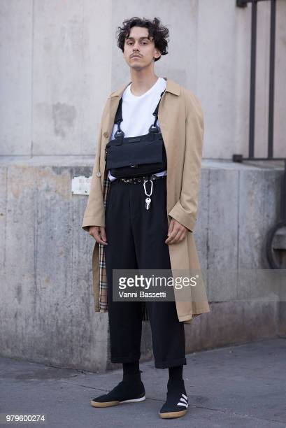 A guest poses wearing a Burberry trench coat Adidas shoes and Nike waist bag after the Off White show at the Theatre National de Chaillot during...