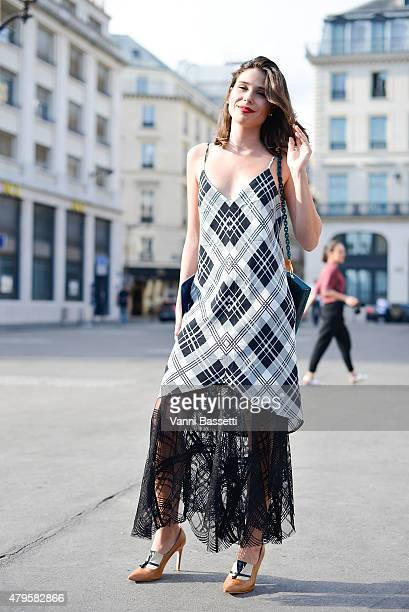 A guest poses wearing a Cris Barnos dress Fabiana Milazo bag and Sarah Chofarian shoes after the Atelier Versace show at the Palais Brogniart on July...