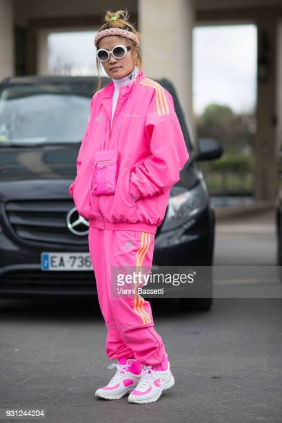 A guest poses wearing a Gosha Rubchinskiy X Adidas pink tracksuit and Chanel sneakers after the Miu Miu show at the Palais de Iena during Paris...