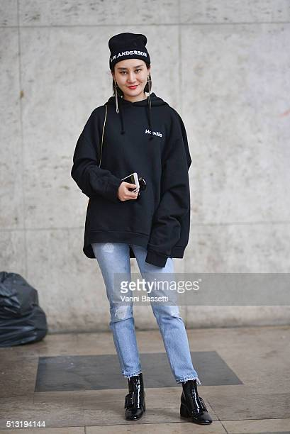 A guest poses wearing a JW Anderson beanie Vetements sweatshirt and Miu Miu shoes before the Anrealage show at the Palais de Tokyo during Paris...