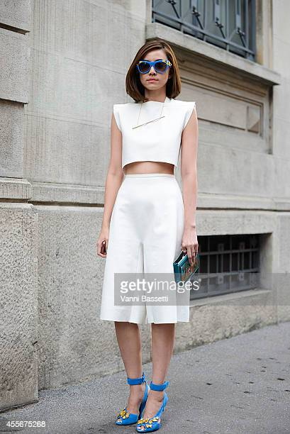 A guest poses wearing a Prada shirt clutch sunglasses and shoes and Realistic Situation trousers on September 18 2014 in Milan Italy