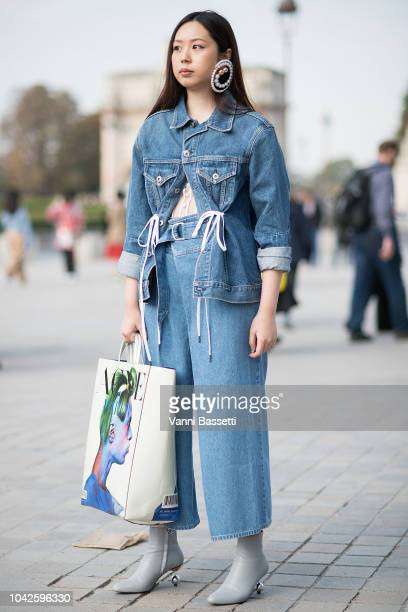 A guest poses wearing a Proenza Schouler denim jacket and an Acne Studios bag after the Each X Other show at the Carrousel du Louvre during Paris...