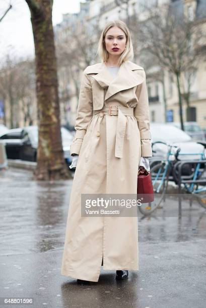 A guest poses wearing a See by Chloe trenchcoat after the Valentin Yudashkin show at the Palais de Tokyo during Paris Fashion Week Womenswear FW...