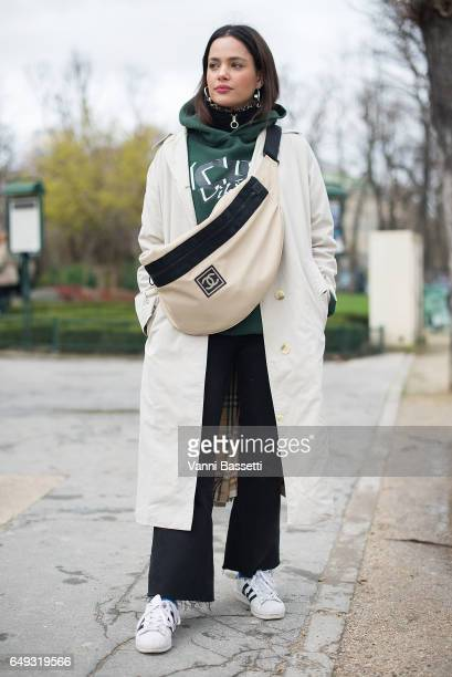 A guest poses wearing a trenchcoat Chanel bag and adidas superstar shoes after the Chanel show at the Grand Palais during Paris Fashion Week...